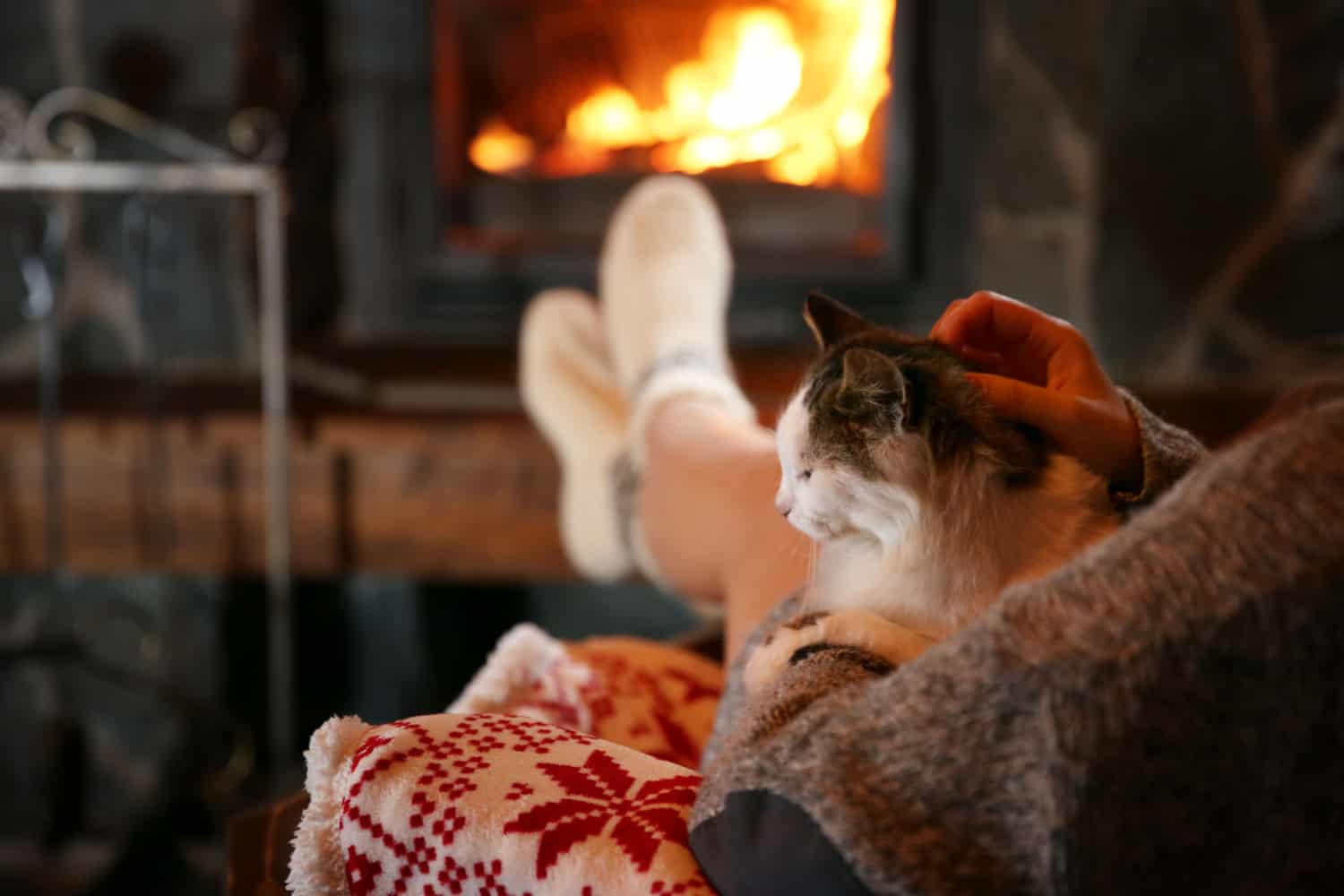 A woman is resting with a cat near a fireplace
