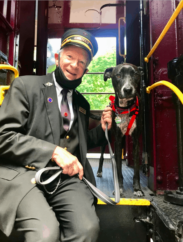 Happy conductor of a train sitting next to a dog with colored silence in red harness on the scenic Leigh Gorge Railroad in Jim Thorpe, PA