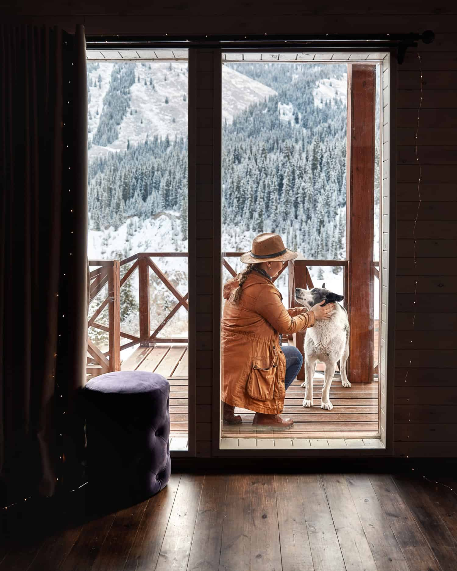 A woman in a hat plays with her dog on the deck of a winter holiday pet property