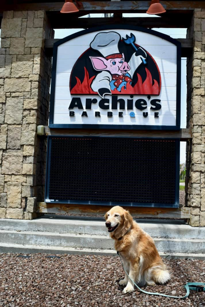 The Golden Retriever sits in front of the Archies barbecue sign